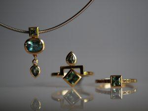 Schmuckstücke aus dem Goldschmiede Meisteratelier Höfelmaier im modernen und straighten Design. Anfertigung aus 750/000 Gelbgold. Der Anhänger besteht aus folgenden Edelsteinen - oben ein grüner Saphir im Carréschliff, darunter ein grüner Beryll im Ovalschliff, dann ein Diamant und ganz unten ein grüner Saphir im Tropfenschliff. Der Ring in der Mitte verbindet einen moosgrünen Turmalin mit einem grünen Saphir. Der Ring rechts zeigt einen moosgrünen Turmalin im Carréschliff und Brillanten in der Farbe Champagner.