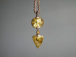 Im Goldschmiede Meisteratelier Höfelmaier wurde dieser 925/000 Silber Schmuck gefertigt. Der Anhänger zeigt Bergkristalle (Quarz) mit sternförmig angeordneten Rutilnadeln. Der obere Stein ist oval, der untere in Lanzett-Form. Verbunden werden die beiden Bergkristalle mit einem gelben Saphir.