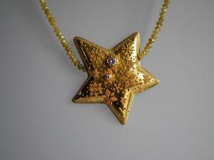 Im Goldschmiede Meisteratelier Höfelmaier wurde dieser Anhänger gefertigt, aus 900/000 Gelb Gold mit Granulation, eine antike Goldschmiede Technik Stern mit Sternenmotiv, symbolisiert das Universum und den Sternenstaub, Champagner Farbe Diamantkette weiße Brillanten, Diamanten