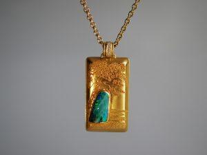 """Auf dem Bild sehen Sie einen Anhänger, gefertigt in 900/000 und 750/000 Gelbgold. Ein phantastisches Werk aus dem Atelier Höfelmaier. Das Schmuckstück ist rechteckig und stellt ein Bild dar. Auf diesem Bild wurde in Granulationstechnik eine Landschaft """"gemalt"""". Es zeigt einen Fels, bestehend aus einem feinen Boulder-Opal, auf dem ein Baum gegen den Himmel wächst. Die """"Zeichnung"""" ist aus kleinsten Goldkügelchen gelegt. Die Granalien wurden der Größe nach sortiert und je weiter man in die Landschaft blickt, werden die Kugeln kleiner. Somit entsteht eine optische Tiefenwirkung und ein """"Sfumato"""", eine Maltechnik, die in der Renaissance erfunden wurde."""