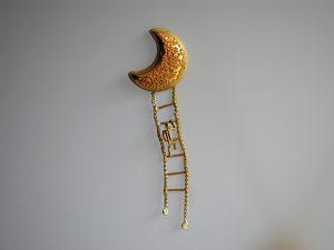 """Auf diesem Foto sehen Sie """"den Mondkletterer"""". Es ist eine Anstecknadel aus dem Atelier Höfelmaier. An einer granulierten Mondsichel, bestehend aus 900/000 und 750/000 Gelbgold, hängt eine Strickleiter aus Goldkettchen gefertigt, an dem ein Männchen hinaufsteigt. Unten an den Enden des """"Seiles"""" sind zwei Brillanten angebracht."""