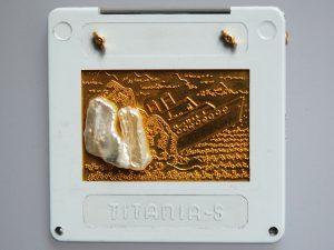 """Hier sehen Sie eine Brosche aus dem Atelier Höfelmaier, gefertigt aus 900/000 und 750/000 Gelbgold. Es ist ein goldenes Bild in einen herkömmlichen Diarahmen gesetzt worden. Da der Diarahmen den Firmennamen """"Titania"""" trägt, ist auf dem Bild auch der Untergang der Titanic zu sehen. Das arme Schiff hat einen Eisberg gerammt, hier durch eine Süßwasserperle dargestellt. Die Brosche hat einen Titel: """"Hybris""""."""