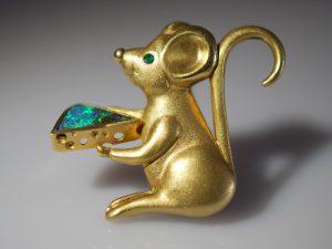 Eine wertvolle Brosche aus dem Goldschmiede Meisteratelier Höfelmaier zeigt eine kleine Maus mit Käse. Gefertigt wurde diese Brosche aus 750/000 Gelbgold und den Edelsteinen australischer Boulder Opal, sowie dem Auge mittels einem Smaragd.