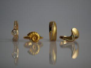 Im Goldschmiede Meisteratelier Höfelmaier wurden diese vier Ringe aus 750/000 Gelbgold gefertigt. Die verwendeten Edelsteine sind weiße Diamanten im Brillantschliff als klassischer Solitär, mit Brilliant im Ammonit, mit Brillanten im Ring konvex konkav und mit Brillanten im Ring Welle.