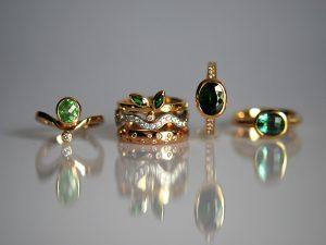 Sechs elegante Ringe aus dem Goldschmiede Meisteratelier Höfelmaier in 750/000 Gelbgold. Die Ringe zeigen folgende Edelsteine von links nach rechts - Tsavorit Oval Diamant, Ring Tsavorite im Navette-Schliff ,Brillant, Ring Turmalin moosgrün, Schachbrettschliff, oval, Diamanten im Brillantschliff