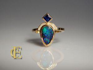 Opalring mit blauem Saphir im Caré Schliff und Brillantbogen